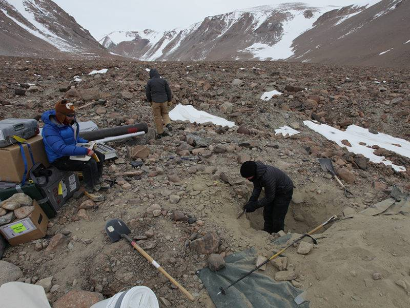 Researchers in Ong Valley, Antarctica, take pit samples above the ice during a field mission. Pictured left to right: Dan Morgan (Vanderbilt University), Greg Balco (Berkeley Geochronology Center), and Marie Bergelin (University of North Dakota, Grand Forks). Credit: Jaakko Putkonen
